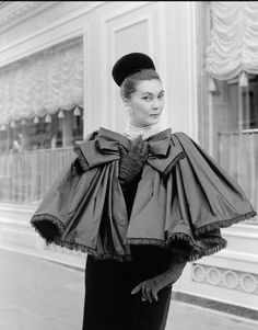1959 Alla in fringed satin capelet tied in large bow worn over slim velvet dress by Yves Saint Laurent, photo by Willy Maywald, Paris