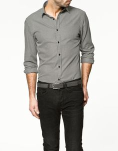 Grey shirt with rolled up sleeves. Black pants. Grey belt.