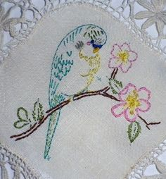 Budgie embroidered on lace doily