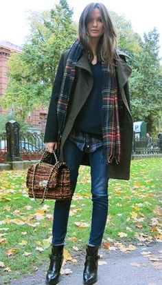 Columbine Smille in a forest green coat, tartan scarf, skinny jeans, and shiny heeled boots