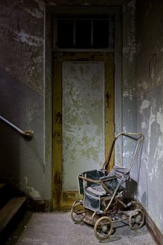 A pram sits on the landing of a stairwell in the Lincoln Ward - Worcester State Hospital, MA
