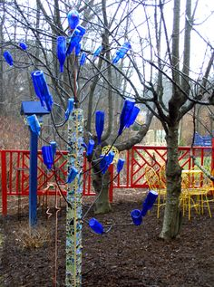 For teaching colours and to liven up a winter yard, having the children paint or collect items of one colour, assist with stringing them together, and helping to hang them up in the trees could be a multiple learning activity. Wine Bottle Art, Blue Bottle, Wine Bottle Crafts, Bottle Garden, Glass Garden, Garden Totems, Garden Crafts, Garden Projects, Bottles And Jars