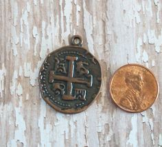 A personal favorite from my Etsy shop https://www.etsy.com/listing/242135160/antiqued-copper-pewter-cross-coin-charm