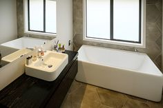 Brodie & Niki Retallick's bathroom with extra long free standing white bath, black vanity and grey floor and wall hexagon tiles #house #bathroom #bath #interiordesign #brodieretallick #generationhomes