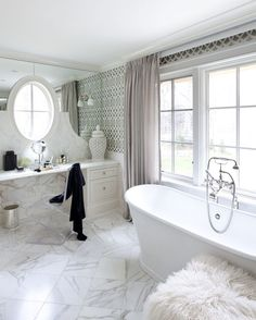 """Modern New England Style - """"Like in the kitchen, Eastman and her clients opted for classic fixtures and materials in the master bath, pairing them with modern items like the mohair stool, Lucite chair, and Imperial Trellis wallpaper for a fun twist."""""""
