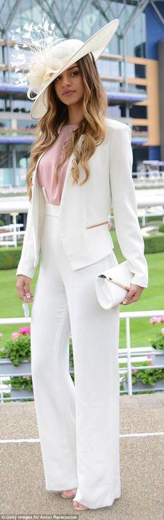 A racegoer stunned in an elegant white trouser suit...