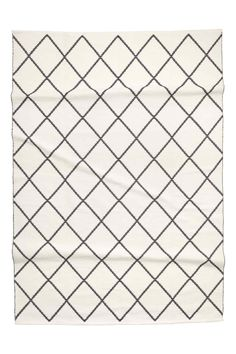 Large cotton rug with a jacquard-weave pattern.
