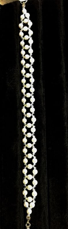 This Beautiful bracelet is made with small Swarovski pearls and has the look of lattice work. It lays flat on the wrist and will be a eye catcher. Perfect for the Bride or can be ordered with accent c