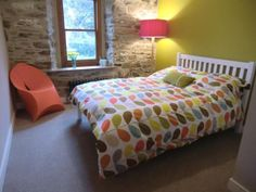 Exposed stone wall, cast iron radiators a definate bolt hole. (love the Orla Kiely)