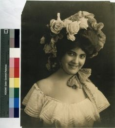 I would totally wear this bonnet to impress a dashing gent. Woman in peasant blouse and flowered hat. (1905)