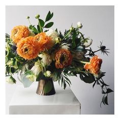 @mimosastyle uses orange ranunculus, thistle, and greens for this wild and beautiful flower arrangement in an Antique Brass Scalloped Pedestal Bowl.: