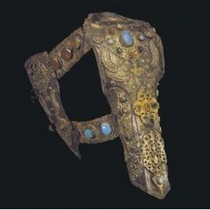 CHAMFRON WITH CHEEK-PIECES  MTW0995    Chamfron (armour for a horse's face) and cheek-pieces. The steel chamfron is set decorated with silver-gilt appliqués and set with jade, carnelian, agate and coloured glass. These materials are characteristic of the decorative armour of parade horses and camels in the Ottoman period    Ottoman Turkey or Egypt 18th century   54.5 x 74 cm