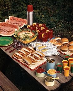 PICNIC TABLE TOP FULL OF FOOD CORN HOT DOGS HAMBURGERS WATERMELON SALAD THERMOS CONDIMENTS BACKYARD SUMMER MEAL Stock Photos