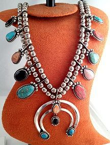 This Sterling Silver squash blossom necklace was crafted and signed by Native American artist 'F'. It was purchased from an estate in Southwest America. It features multiple types, shapes and sizes of stones scallop bezel set in the naja and on the side pendants including Turquoise, Coral, Spiny Oyster and Jet, all accented with silver beads and twist wire ...