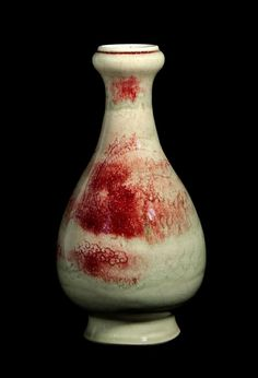 Chinese pear-shaped bottle vase with bulbed rim, incised decoration beneath a pale celadon glaze with dragons amongst cloud scrolls and random splashes of ox blood red.