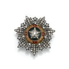 FRENCH SOMALILAND ORDER OF NICHAN EL-ANOUAR Miniature size breast star, enhanced with green and red enamel, and set with circular- and rose-cut diamonds, height approximately 31mm, removable brooch fitting