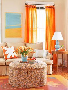des rideaux orange et des coussins en blanc et orange dans la salle de séjour