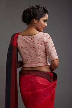 White & red pinstriped blouse has a peplumwaist band that gives it an old world charm. Hand-block printing detail adds to the quaint look. THE KAITHAR...