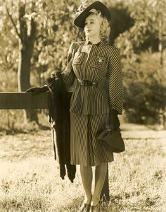 Carole Landis in a wonderful striped skirt suit, 1941 vintage fashion style pinstripe wool suit jacket skirt stripes 40s glam movie star day wear photo portrait girl near hitching post hat gloves shoes purse fur wrap war era WWII movie star model