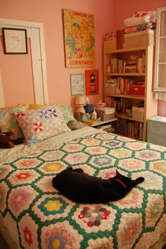 Homely bedroom with adorable patchwork quilt and pillows. Cherry blossom pink paint and interesting art work graces the walls, whilst the pretty little shelf is crammed with all sorts of books and ornaments.