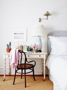 A feminine bedside table and chair in white bedroom.