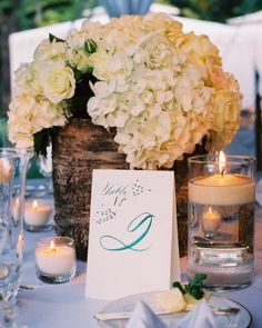 A mano     ---- Calligraphed Table Card  Tented table numbers incorporated the teal-blue calligraphy that was seen throughout the rest of this real wedding.