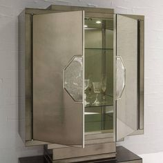 This magnificent cabinet is a modern interpretation of a piece by Jacques-Emile Rhulmann (1879-1933) and features geometric shapes that create an impressive objet d'art with a central engraved decoration adorning the front panels covering the doors