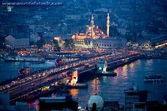 The Galata Bridge And The New Mosque Glow And Reflect In The Golden Horn As Dusk Falls Over The City. Istanbul, Turkey