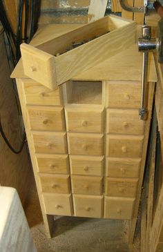 Shop cabinet simply made using scrap plywood (fronts are wood with a dowel for a pull). Bins can be carried to where the work is. Small item storage such as screws and router bits.
