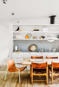 worktable, shelves and cabinets against the wall, light colors with wood floors, small earthen color pops
