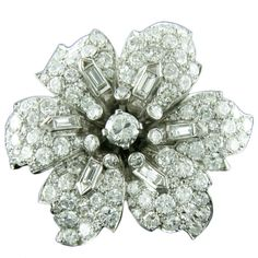Exquisite Antique Diamond Flower Brooch  Unknown  Circa 1905  Magificent platinum and diamond flower shaped brooch Circa 1905. This elegant pin consists of round brilliant cut diamonds covering each petal with a single baguette at the base 6 total and a round brilliant cut diamond center stone encircled by smaller round brilliant cut diamonds making up the stamen of the flower.