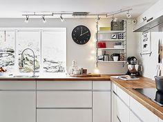 Muebles blancos, encimera de madera y electrodomésticos de acero