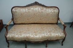 Antique carved wood settee with silk floral upholstery.