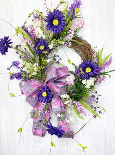 Pretty in purple! This gorgeous Spring or summer wreath with purple flowers and plaid pink bow is absolutely stunning. Add it to your door to brighten up your summer home decor. Get the kit and/or watch the tutorial by Keleas Floral on our Facebook Page. Spring Wreaths, Summer Wreath, Front Door Decor, Wreaths For Front Door, Spring Decorations, Summer Ideas, Diy Wreath, Absolutely Stunning, Home Decor Inspiration