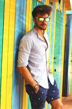 Acheter+la+tenue+sur+Lookastic:+https://lookastic.fr/mode-homme/tenues/blanc-short-bleu-marine-et-blanc-lunettes-de-soleil-jaune-montre-vert-et-rouge/2621+ —+Lunettes+de+soleil+jaune+ —+Chemise+à+manches+longues+à+rayures+verticales+blanche+ —+Short+imprimé+bleu+marine+et+blanc+ —+Montre+en+nylon+à+rayures+horizontales+vert+et+rouge+