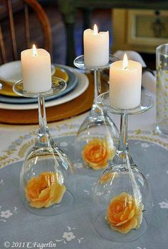 Candle holders made from wine glasses. Red rose instead and a silver ribbon beautiful simple center piece for wedding