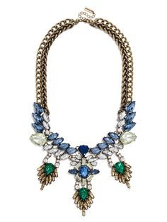 This stunning bib has lots of movement--fringed emeralds add drama to the silhouette, while sapphire gemstones come together in an ornate marquise-lined collar.
