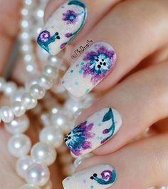Get to draw beautiful watercolor flowers on your nails. Use cool colors such as blue and violet and even add cute details such as little small snails crawling around.