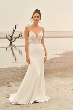 Highlight your figure and turn heads as you walk down the aisle in this spaghetti strap illusion beaded bodice fit and flare gown. The chapel length train completes the look.