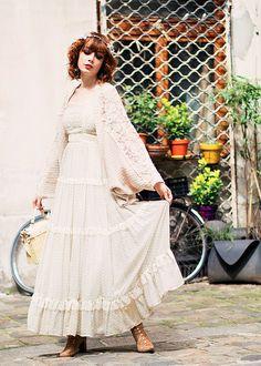Longue robe de dentelle sous un gilet de maille confortable, jolies bottines lacées et fleurs dans les cheveux