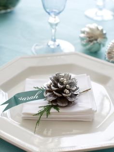 Each place setting can be dressed up with a pinecone and name tag cut from scrapbook paper and attached to a whitewashed pinecone studded with silver dragees.