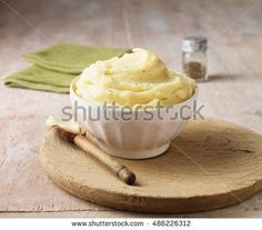 Ultimate mashed potato with black pepper in white faceted bowl with wooden spoon - Shutterstock Premier