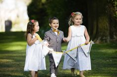 Adorable group of flower girls and paige boy carrying here comes the bride flag sign!