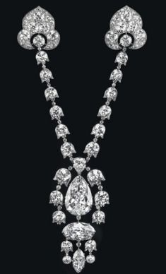 A Belle Époque Diamond Devant-de-Corsage Brooch, by Cartier – The pendant centering upon a pear-shaped diamond, weighing approximately 34.08...