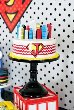"""Our local Super Target sold a round two-layer white cake for $12, and we embellished it to look like a custom decorated superhero cake,"" Maureen Anders says of the cake for her superhero-themed party. The party planner added a chevron ribbon, a yellow Lemon Head candy border, and a printable skyline to jazz up the cake. Source: Anders Ruff"