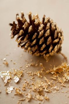 DIY gold leaf pine cones make a festive garland for the mantel.
