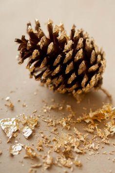 DIY gold leaf pine cones make a festive garland for the mantel.