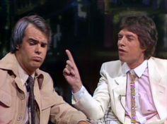 Dan Aykroyd, as Tom Snyder, interviewing Mick Jagger