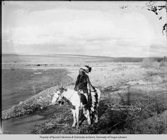 Chief Uma -Som-Kin Walla Walla TribeAn outside photograph of a Native American man, who has been identified as Uma-Som-Kin. He is dressed in full native regalia, and sitting on a horse that is standing next to a river's edge. For his headdress, the man is wearing a bonnet with a single trail of eagle feathers. He is wearing a coat made out of a Pendleton blanket. He is wearing leggings that exhibit a geometrical design on the cuff--perhaps beaded--and beaded moccasins. Because no stirrups can be