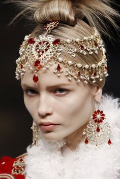 Alexander McQueen  Nude and Soft makeup accompanied by big floral earrings and also the princess-like crown jewellery embeliishment on the forehead with a semi push-back hairdo giving a stiff hair-end blooming at the back.